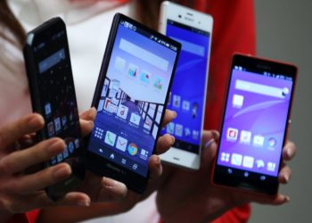Models hold Fujitsu Ltd. Arrows, from left, Sharp Corp. Aquos Zeta, Sony Corp. Xperia Z3 and Xperia Z3 Compact smartphones during a news conference unveiling NTT Docomo Inc.'s new smartphone models in Tokyo, Japan, on Tuesday, Sept. 30, 21014. NTT Docomo, Japan's largest mobile phone company, introduced 16 mobile devices for winter and spring today. Photographer: Tomohiro Ohsumi/Bloomberg via Getty Images