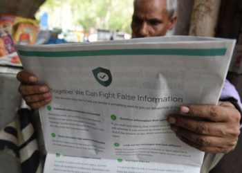 This photo illustration shows an Indian newspaper vendor reading a newspaper with a full back page advertisement from WhatsApp intended to counter fake information, in New Delhi on July 10, 2018. - Facebook owned messaging service WhatsApp on July 10 published full-page advertisements in Indian dailies in a bid to counter fake information that has sparked mob lynching attacks across the country. (Photo by Prakash SINGH / AFP)        (Photo credit should read PRAKASH SINGH/AFP/Getty Images)