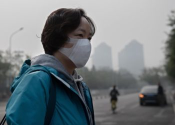A woman wears a protective mask to fight bad air pollution in Beijing on October 22, 2018. (Photo by Nicolas ASFOURI / AFP)        (Photo credit should read NICOLAS ASFOURI/AFP/Getty Images)