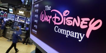 FILE - In this Aug. 8, 2017, file photo, The Walt Disney Co. logo appears on a screen above the floor of the New York Stock Exchange. European Union authorities say they have cleared Disney's acquisition of Fox's entertainment assets, provided Disney sells off some TV channels it controls in Europe. The European Commission said Tuesday, Nov. 6, 2018 it gave its approval to the deal under the EU Merger Regulation. (AP Photo/Richard Drew, File)