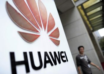 In this Monday, Oct. 8, 2012 photo, a man walks near a logo at a R&D center of Huawei Technologies Inc. in Wuhan, in central China's Hubei province. Eager to expand in the United States, China's biggest technology companies face American anxiety about security and rising Chinese competition. (AP Photo)  CHINA OUT