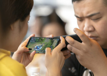 XI'AN, SHAANXI PROVINCE, CHINA - 2018/05/30: Young lovers concentrate on playing video games on mobile phones in a cafe. (Photo by Zhang Peng/LightRocket via Getty Images)
