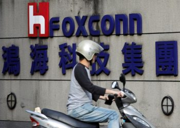 FILE PHOTO: A motorcyclist rides past the logo of Foxconn, the trading name of Hon Hai Precision Industry, in Taipei, Taiwan March 30, 2018. REUTERS/Tyrone Siu/File Photo